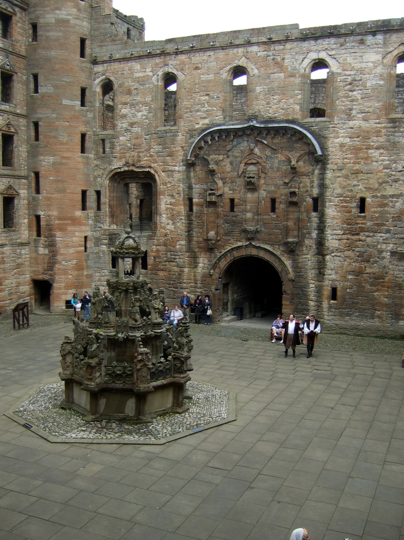 Courtyard and fountain of Linlithgow Palace, a large, ruinous and impressive royal residence of the monarchs of Scotland and birthplace of Mary, Queen of Scots, in a scenic location in a park with a pond in the historic burgh of Linlithgow.