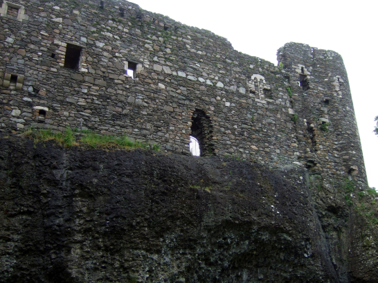 Curtain wall of Dunstaffnage Castle, an impressive but grim old ruinous walled castle, long held by the Campbells, with later tower and atmospheric chapel in a wooded spot near Oban in Argyll.