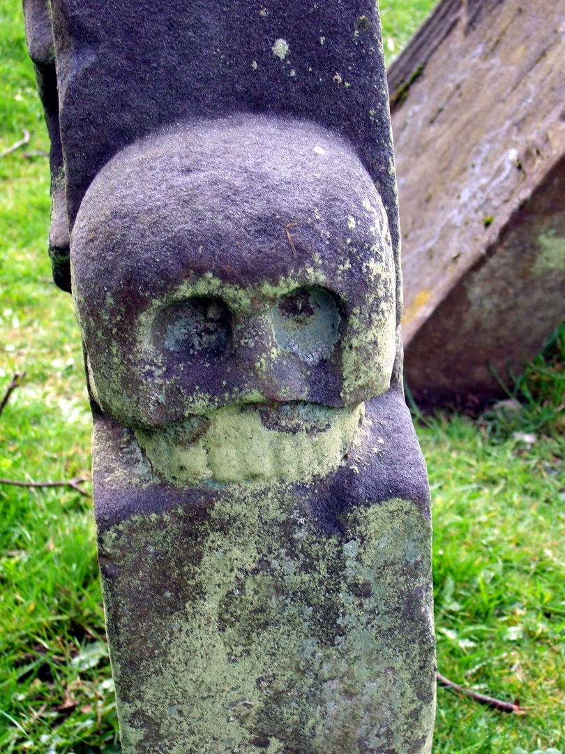 Carved gravestone with skull, St Bridget's Kirk at Dalgety is a fascinating old church with a domestic block at one end, built by the Setons, in a pretty wooded spot by the sea, near the new town of Dalgety Bay in Fife in central Scotland.