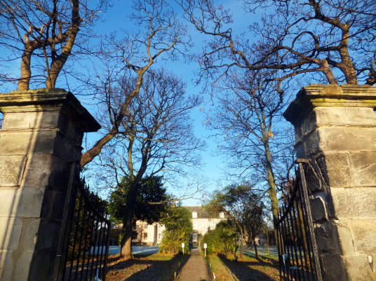 Gates of the main entrance of Cockenzie House, a long plain mansion with some old interiors, dating from the 17th century, in beautiful gardens in the pleasant town of Cockenzie and Port Seton on the banks of the Firth of Forth, near Prestonpans in