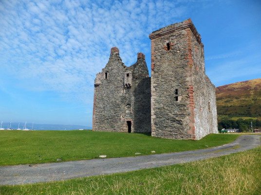 Lochranza Castle, an imposing old ruinous fortress, standing on a spit of land in a stunningly beautiful spot at Lochranza to the north of the mountainous island of Arran on the west coast of Scotland.