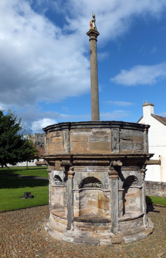 Preston Mercat Cross, near Preston Tower, a tall, impressive and grim old tower house, long held by the Hamiltons and in fine gardens in Prestonpans in East Lothian in eastern Scotland.