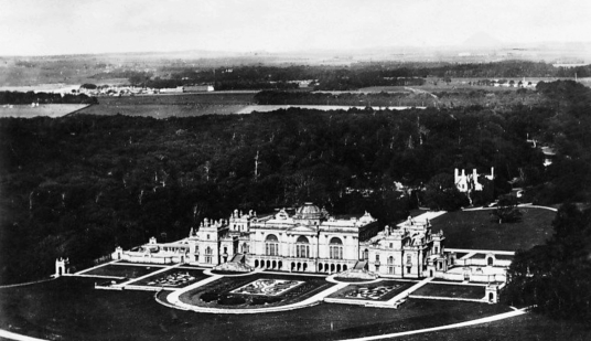 Aerial view of Gosford House, the large and magnificent mansion of the Earls of Wemyss, set in fantastic landscaped grounds with pleasure grounds, woodland and ponds, standing near Longniddry in East Lothian in southeast Scotland on the banks of the Firth