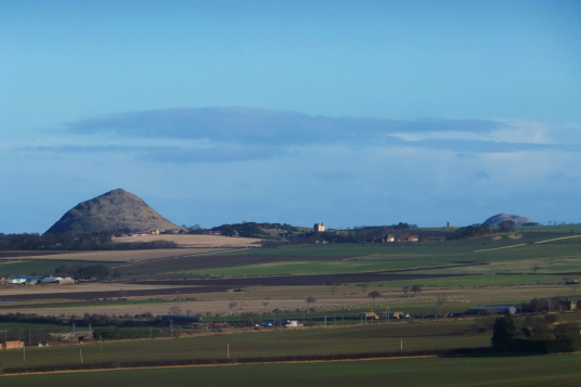 North Berwick Law and Fenton Tower, an imposing old restored tower house in a pretty spot on a hill, held by the Whitelaws, Carmichaels, Erskines and Maxwells, near Kingston and North Berwick in East Lothian in central Scotland.